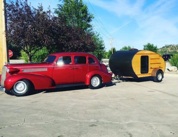 Classic car towing teardrop trailer