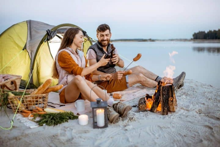 Couple eating meal in front of tent