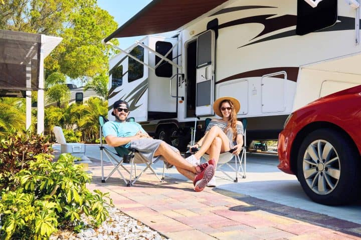Couple sitting in front of 5th wheel at rv park
