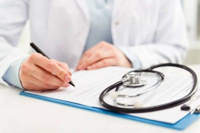 Doctor writing with stethoscope