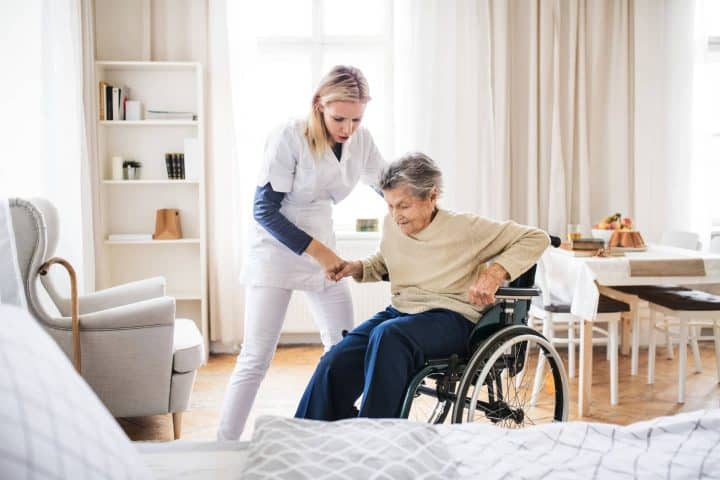 Health care working helping lady in wheelchair