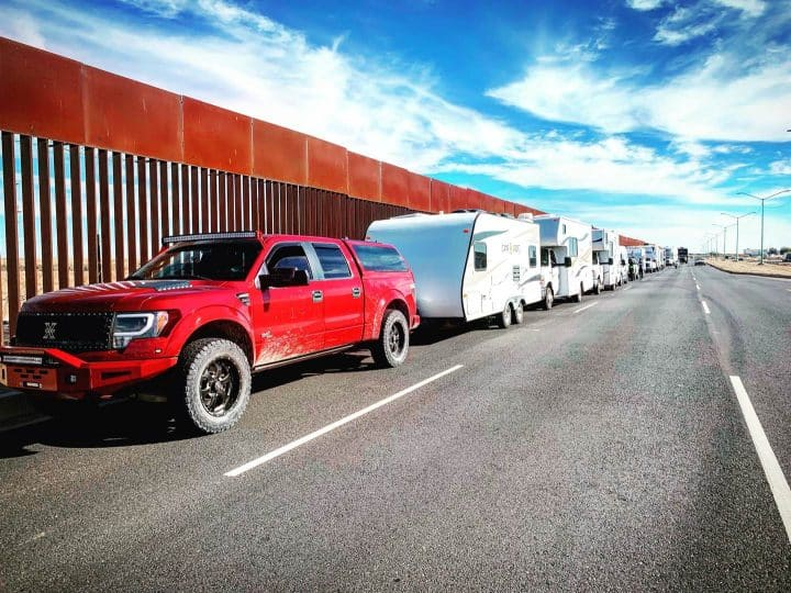 Line of RVs against Mexico border wall