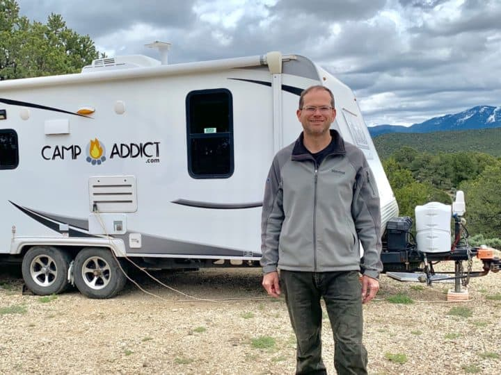 Camp addict co-founder Marshall standing in front of his travel trailer