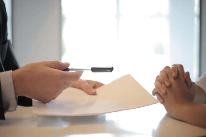 Person handling over paperwork to sign