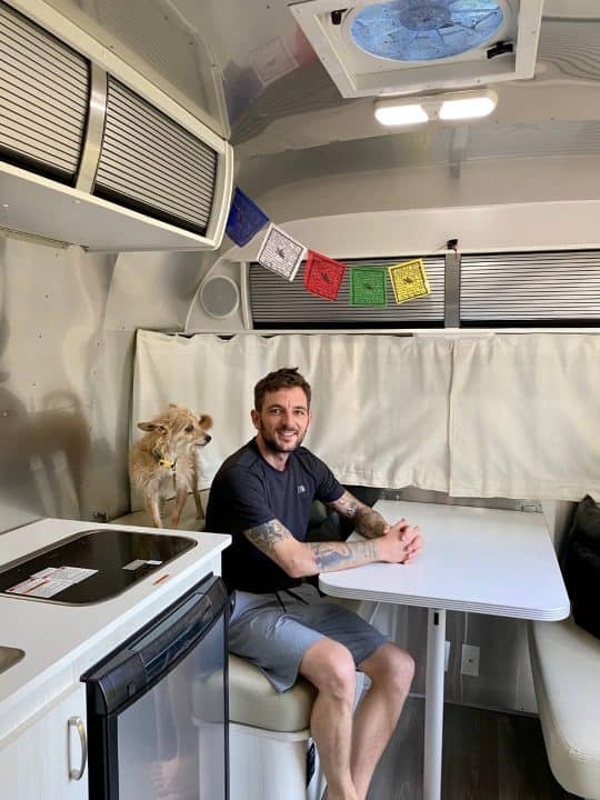 Ray sitting at Airstream Bambi small RV trailer dinette