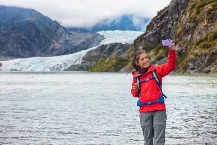Woman tourist taking selfie Mendenhall glacier Juneau Alaska